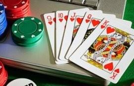 Ilustrační obrázek internetového pokeru. Na obrázku jsou žetony, karty a počítač.