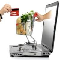 Ruka s kreditní kartou a malý nákupní košík přicházející z obrazovky notebooku.