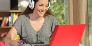Přepisovatelka se sluchátky pracuje na přepisech různých zvukových souborů.